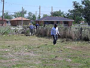 Residents of New Orleans cleaning their backyard following Hurricane Katrina